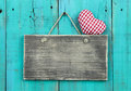 Blank distressed wood sign with red checkered heart hanging on rustic antique teal blue door