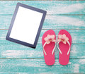 Blank empty tablet computer on beach. Trendy summer accessories on wooden background pool. Flip-flops on beach. Tropical flower or Royalty Free Stock Photo