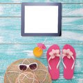 Blank empty tablet computer on beach. Trendy summer accessories on wooden background pool. Sunglasses, orange juice and flip-flops Royalty Free Stock Photo