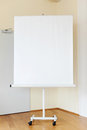 Blank flip chart in boardroom on hardwood floor Stock Images