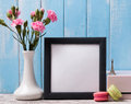 Blank frame, pink flowers and macarons. Royalty Free Stock Photo