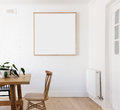 Blank framed print on white wall in danish styled interior dining room