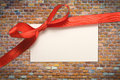 Blank gift tag tied with a bow of red satin ribbon Royalty Free Stock Photos