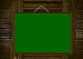 Blank green board on wooden background a hanging a wall Royalty Free Stock Photography