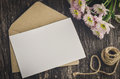 Blank greeting card with brown envelope and white mum flower on wooden table vintage and vignette tone Stock Image