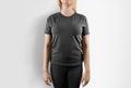 Blank grey t-shirt design mockup. Women stand in gray tshirt Royalty Free Stock Photo