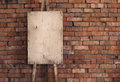 Blank grunge easel on a brick wall Royalty Free Stock Photo