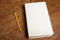 Blank hardcover book hardback with a pencil on an oak wood desktop Stock Photo