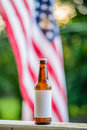 Blank Label Beer Bottle with American Flag in Background Royalty Free Stock Photo