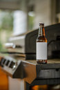 Blank Label Beer Bottle Sitting on edge of Grill Royalty Free Stock Photo