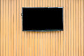 Blank lcd Flat screen television hanging at the wooden wall Royalty Free Stock Photo