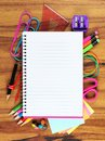 Blank lined notebook with underlying school supply frame on wood Royalty Free Stock Photo