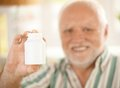 Blank medicine phial handheld in focus by elderly smiling man copyspace Royalty Free Stock Image