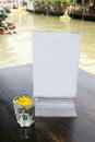 Blank menu stand with shot glass flowers on wood table Stock Photography