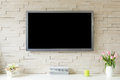 Blank modern flat screen TV at the white brick wall with copy space Royalty Free Stock Photo