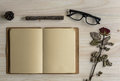 Blank note book with eye glasses on wooden desk Royalty Free Stock Photo