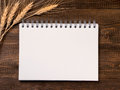 Blank note paper and wheat stalks on wooden background Royalty Free Stock Photo
