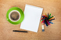 Blank notepad with office supplies and green coffee cup on wooden table above view Stock Photos
