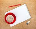 Blank notepad with office supplies and red coffee cup on wooden table above view Royalty Free Stock Photography