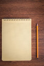 Blank notepad and pencil laying near it on office wooden table Royalty Free Stock Images