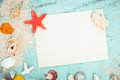 Blank old paper with starfish, shells, coral on wood table background.