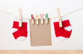 Blank paper with baby socks hanging on love clothesline Royalty Free Stock Photo