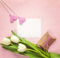 Blank paper card with white tulips, hearts and gift box on rosy Royalty Free Stock Photo