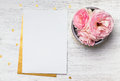 Blank paper and cute pink flowers on white wooden table Royalty Free Stock Photo