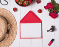 Blank paper, hat, red roses and strawberries on white wooden bac Royalty Free Stock Photo