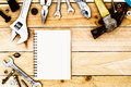 Blank paper notebook With handy tools drops on wooden Background Royalty Free Stock Photo