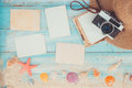 Blank paper photo frames with starfish, shells, coral and items on wooden table Royalty Free Stock Photo