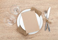 Blank paper on plate wine glasses and silverware set wooden table Stock Photo