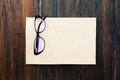 Blank paper and reading glasses on wooden wall Royalty Free Stock Photo