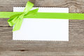 Blank paper sheet with green bow on wooden background Royalty Free Stock Image