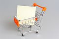 Blank paper sheet in shopping cart on gray Royalty Free Stock Photo