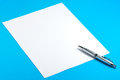 Blank paper sheet silve pen blue background Royalty Free Stock Photo