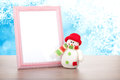 Blank photo frame and christmas snowman on wooden table Royalty Free Stock Photo
