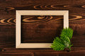 Blank photo wood frame and young green leaves on vintage brown wooden board. Decorative summer background with copy space, top vie Royalty Free Stock Photo