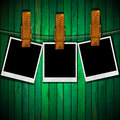 Blank photos hanging on rope three a steel cable green old wall Stock Photos