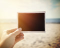 Blank picture photo memory at sunny beach a hand is holding up a snapshot a to add your own or message in the area Stock Image