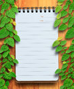 Blank planning notebook on wood background with ivy fixing tree conservation concept Stock Photography