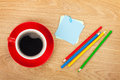 Blank post it with office supplies and coffee cup on wooden table above view Royalty Free Stock Images