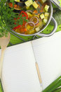 Blank recipe book with vegetable soup kitchen equipment and veggies around them Royalty Free Stock Photos