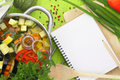 Blank recipe book with vegetable soup kitchen equipment and veggies around them Stock Image