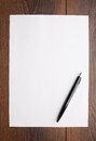 Blank sheet of white paper and pen on a table Royalty Free Stock Images