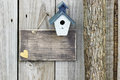 Blank sign with blue and white birdhouse next to tree Royalty Free Stock Photo