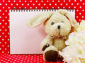 Blank space notebook and cute rabbit doll on red polka dot background Royalty Free Stock Photo
