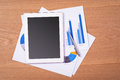 Blank tablet with business chart and pen on wooden table Royalty Free Stock Photo