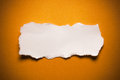 Blank torn paper piece of on an orange surface Stock Image