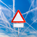 Blank triangular traffic warning sign white on a signpost against a sunny blue sky with crisis crossing contrails from jetliners Stock Image